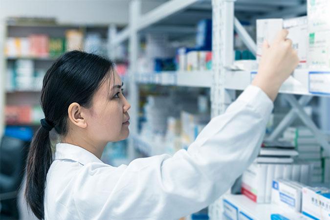 farmacêutica escolhendo medicação em farmácia hospitalar
