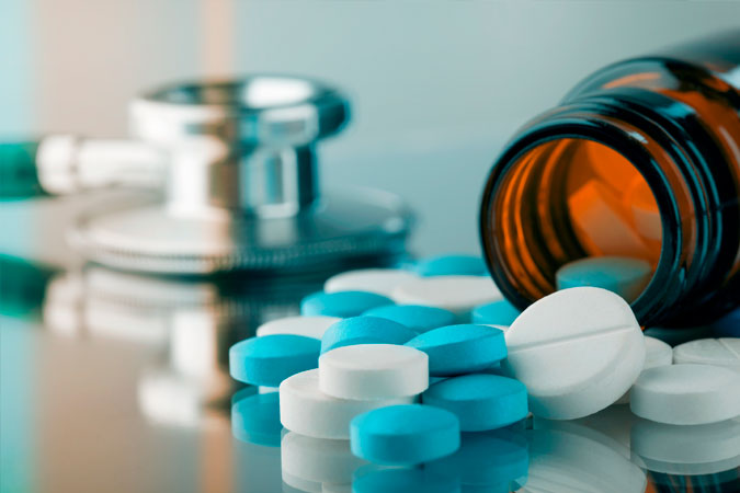 comprimidos ao lado de frasco aberto e estetoscópio