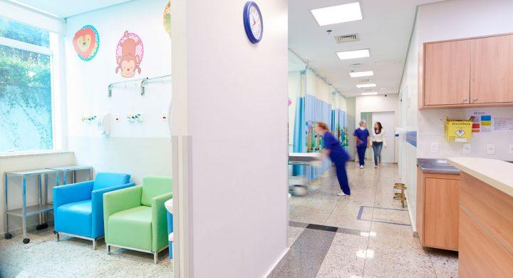 Menina com tranças sendo atendida por uma médica de jaleco e de costas